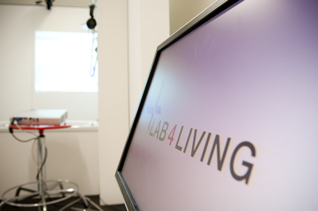 Brand image of PC screen with Lab4Living logo on, in a lab