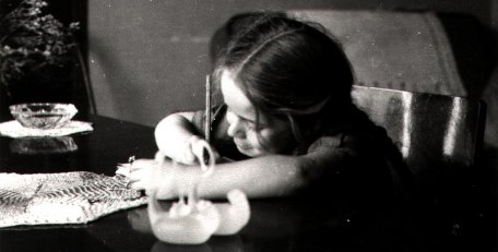 Old Photograph of young girl drawing at the dinning room table